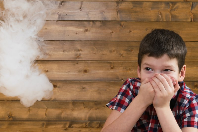 Child covering mouth to avoid secondhand smoke