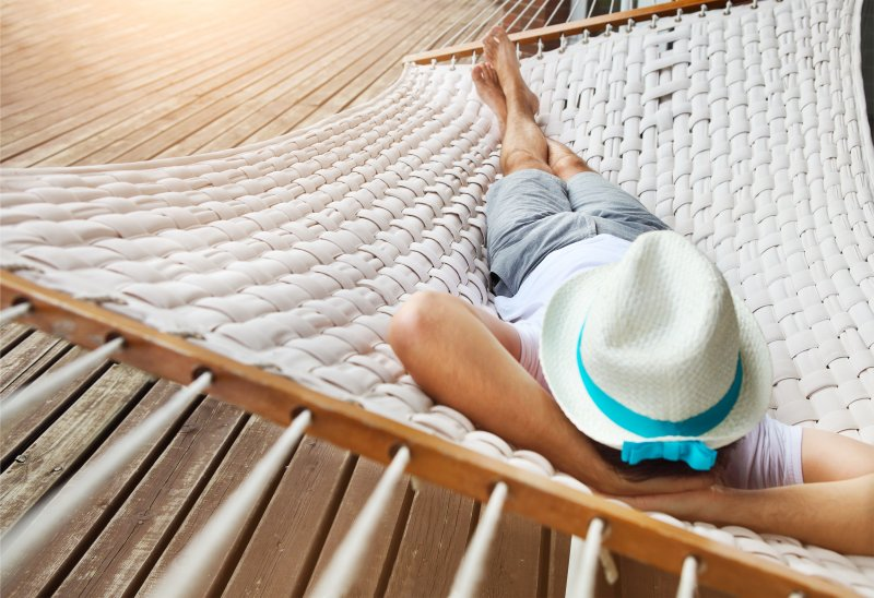 Man with hat sleeping on hammock during the summer