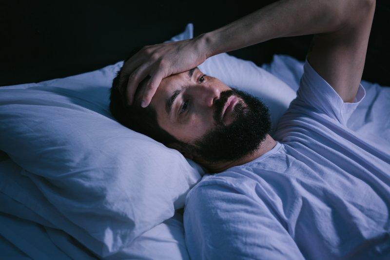 Man lying awake in bed