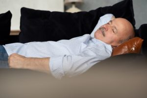 man on a couch napping without sleep apnea treatment