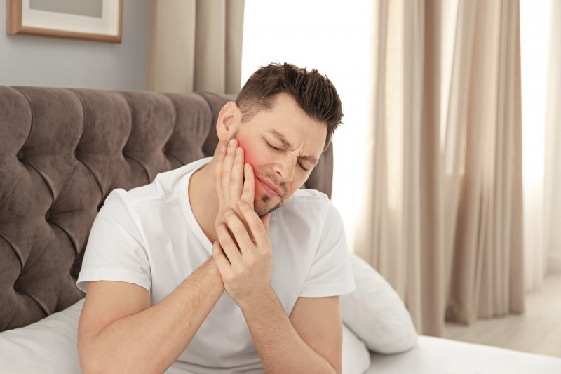 Man suffering jaw pain after waking up in bed